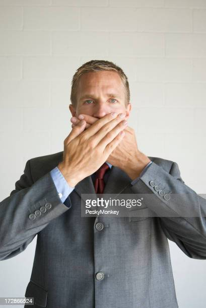 Businessman Covers Mouth to Speak No Evil