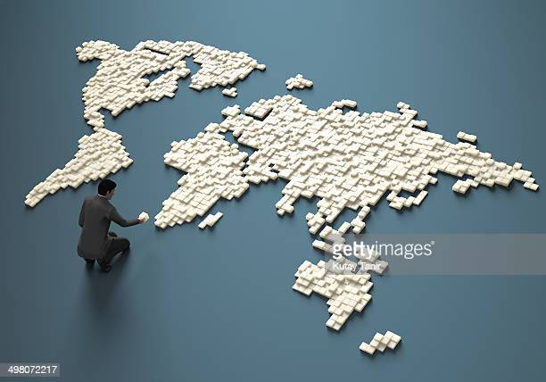 Businessman creating cubes in a world map form.
