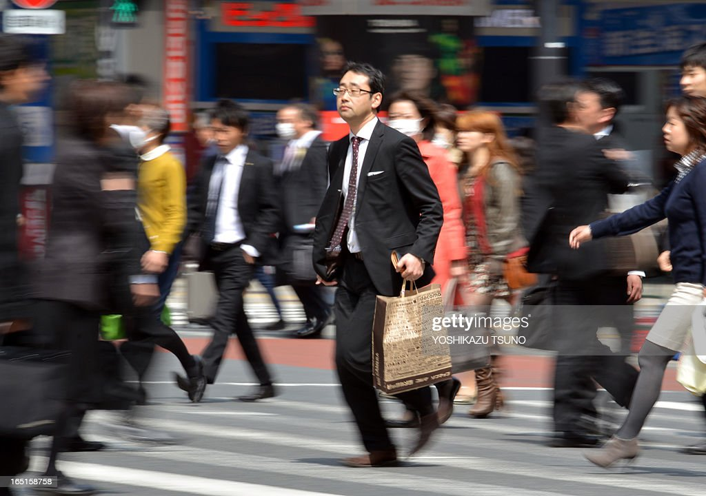 A businessman (C) crosses a road in Tokyo on April 1, 2013. Confidence among large Japanese manufacturers improved in the first quarter, a central bank survey showed on April 1, as Tokyo works to reverse years of limp growth in the world's third-largest economy. AFP PHOTO / Yoshikazu TSUNO