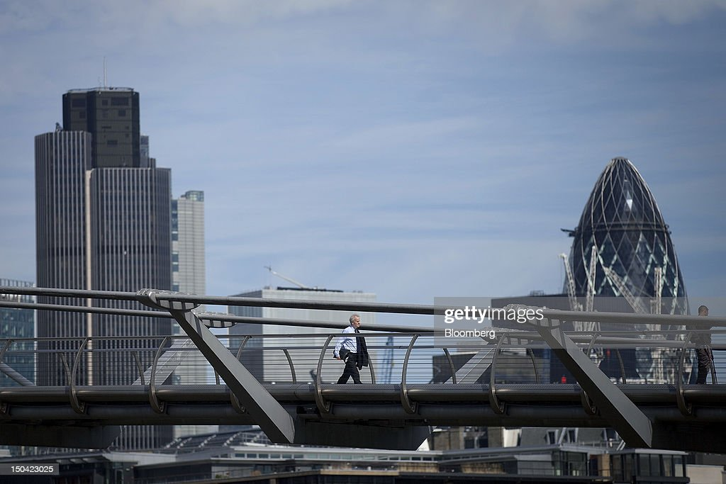 A businessman crosses the Millennium Bridge in front of Tower 42, left, and the Swiss Re Insurance building, right, also known as 'the Gherkin,' in London, U.K., on Friday, Aug. 17, 2012. Banks, insurers and other financial-services firms may eliminate a total of about 3,000 jobs across greater London as companies in the New York region add 9,000, according to U.K.-based researcher Oxford Economics Ltd. Photographer: Simon Dawson/Bloomberg via Getty Images