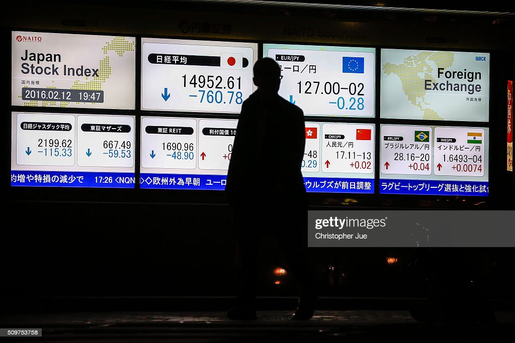 A businessman crosses the street looking at the stock market indicator board on February 12, 2016 in Tokyo, Japan. The Nikkei Stock Average finished 11% down for the week, its biggest weekly drop since October 2008, and the index for the day ended 4.8% down, the lowest since October 2014.