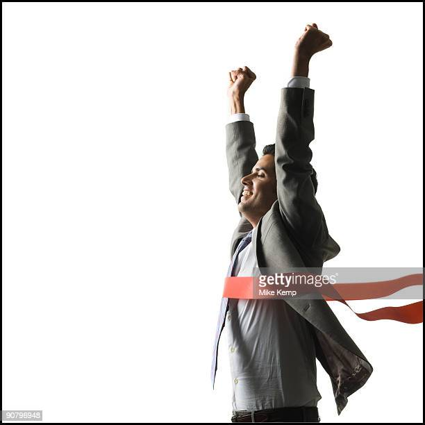 businessman crossing a finish line of a red ribbon with arms raised in the air triumphantly