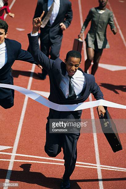 Businessman crossing finish line of race