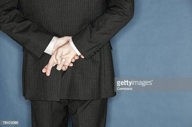 Businessman crossing his fingers behind his back