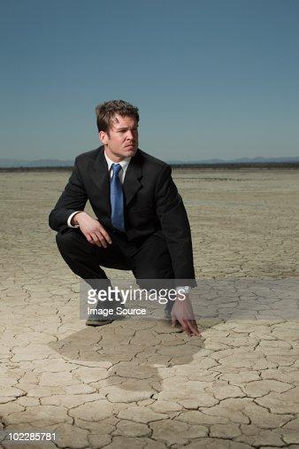 Businessman crouching in desert landscape