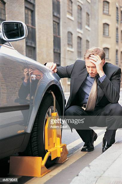 Businessman Crouching on the Kerb Looking Down at His Wheel-Clamped Car
