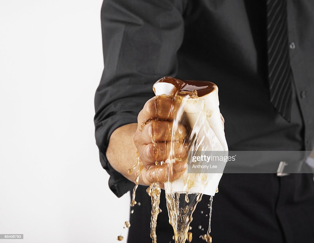 Businessman crushing cup of coffee : Stock Photo