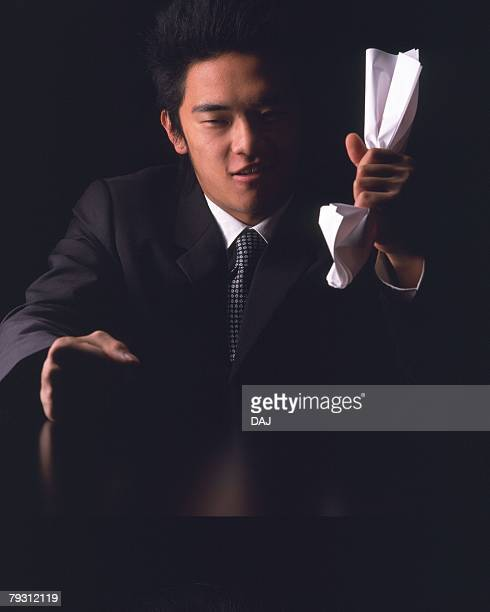 A businessman crushing paper in hand, Front View