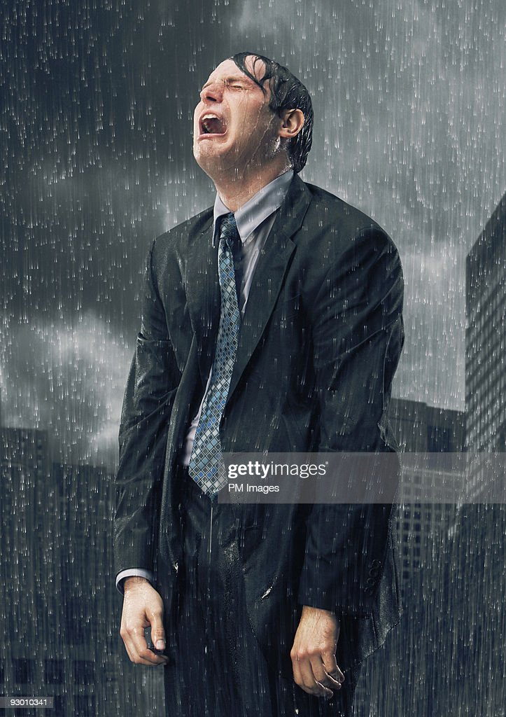Businessman crying in rain : Stock Photo