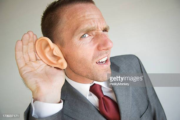 Businessman Cups a Big Ear and Strains to Listen
