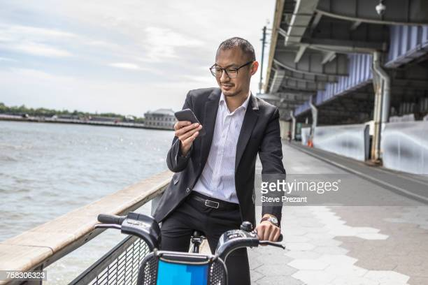 Businessman cyclist looking at smartphone on waterfront, New York, USA