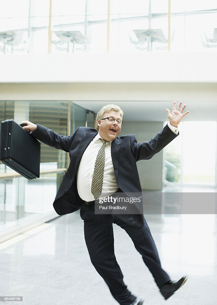Businessman dancing in office lobby : Stock Photo