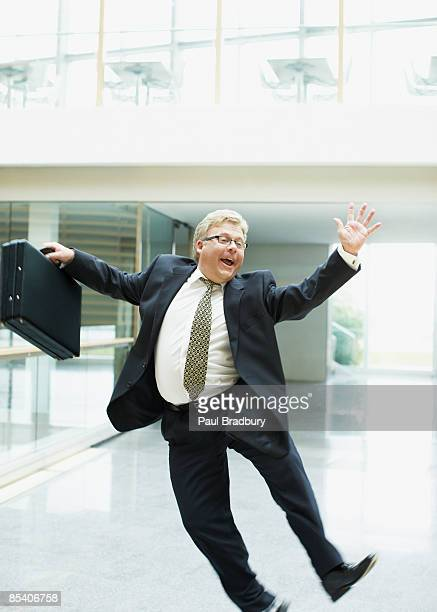 Businessman dancing in office lobby