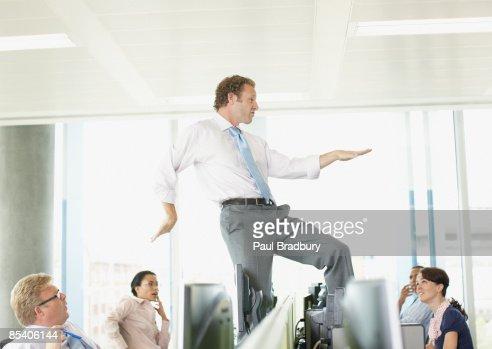 Businessman dancing on cubicle desk