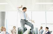 Businessman dancing on desk in cubicle