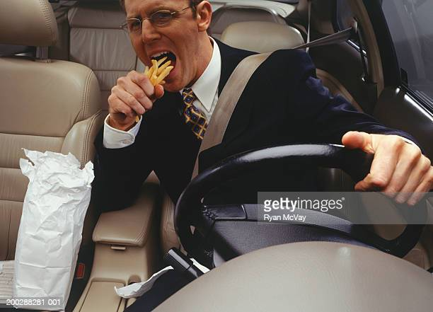 Businessman devouring fries whilst driving car