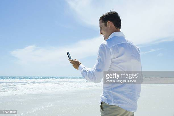 Businessman dialing cell phone on beach