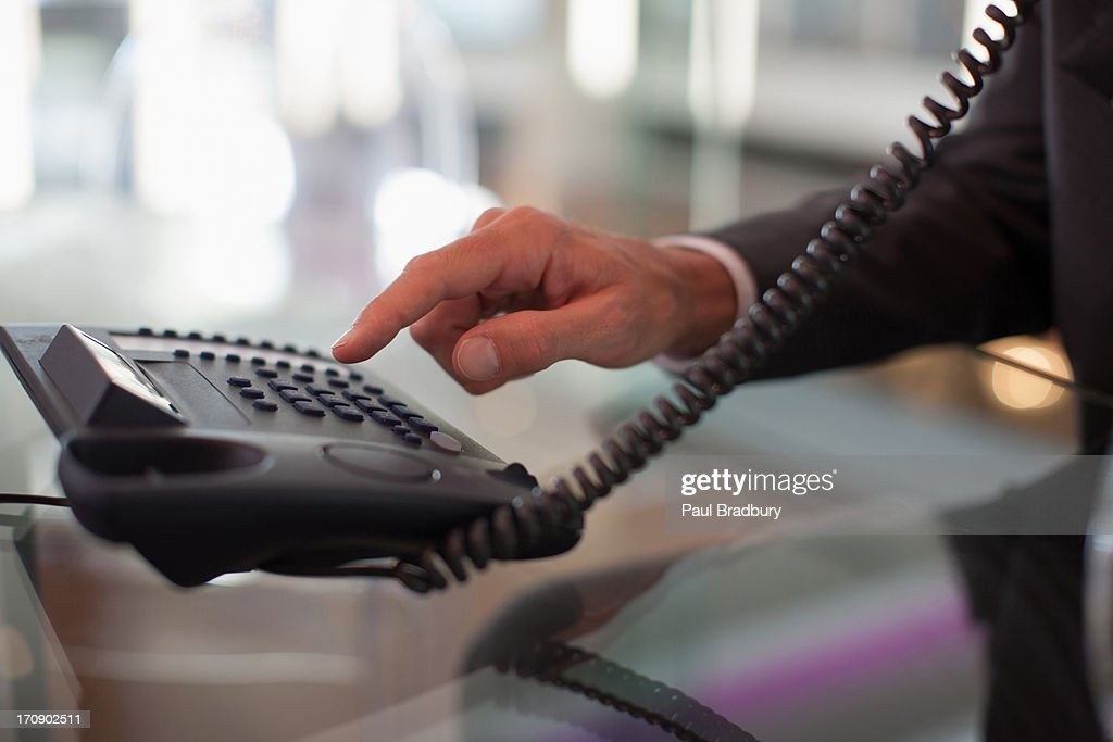 Businessman dialing telephone in office