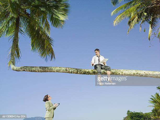 Businessman dictating notes to secretary on beach
