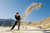 Businessman Digging With Spade in the Desert