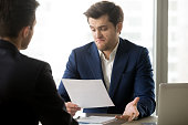 Unsatisfied with contract terms businessman disagrees to accept conditions of questionable agreement meeting with business partner in office. Disappointed investor not impressed with offer concept