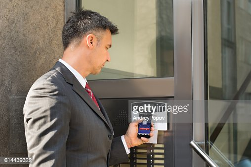 Businessman Disarming Security System Of Door With Smartphone : Stock Photo