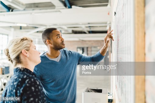 Businessman discussing with colleague over whiteboard