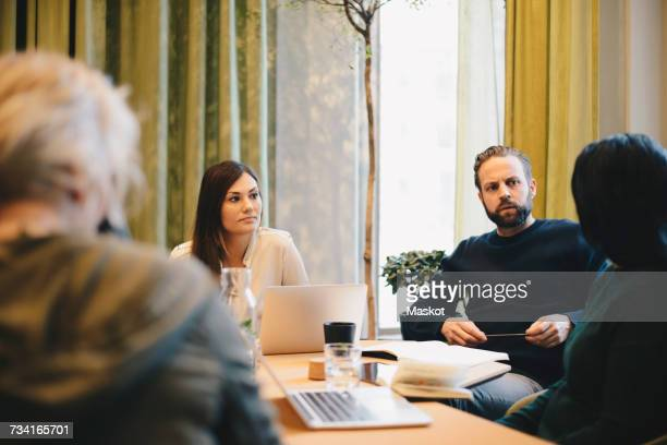 Businessman discussing with colleagues at desk in board room meeting