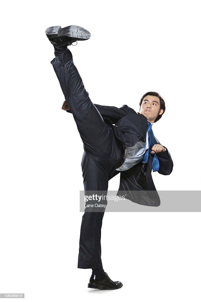 Businessman doing a karate kick