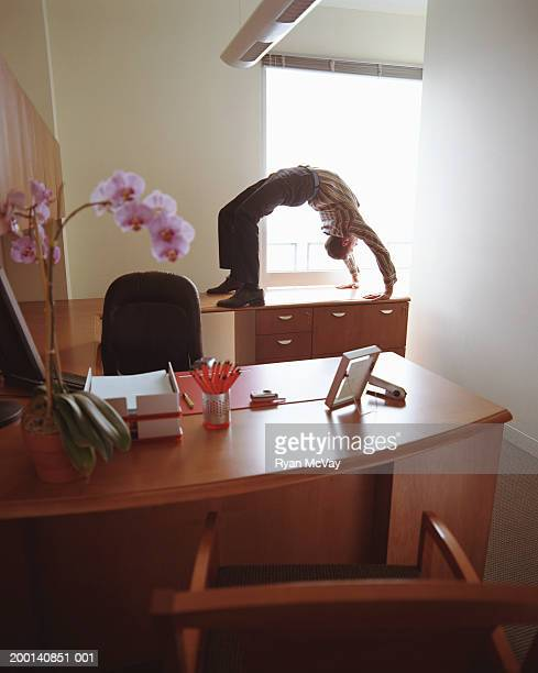 Businessman doing backbend on office desk
