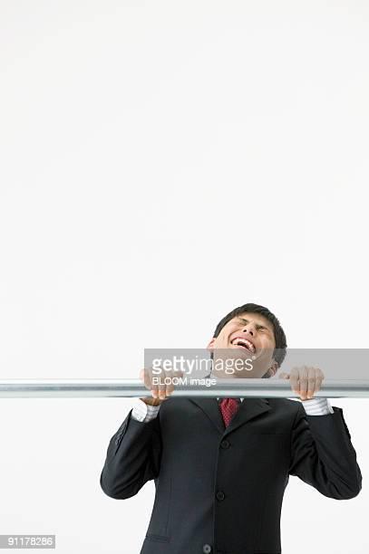 Businessman doing chinning exercises, studio shot, portrait