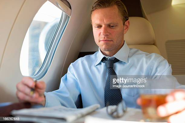 Businessman doing crossword on airplane