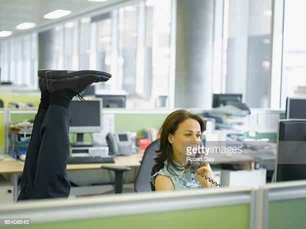 Businessman doing headstand in office