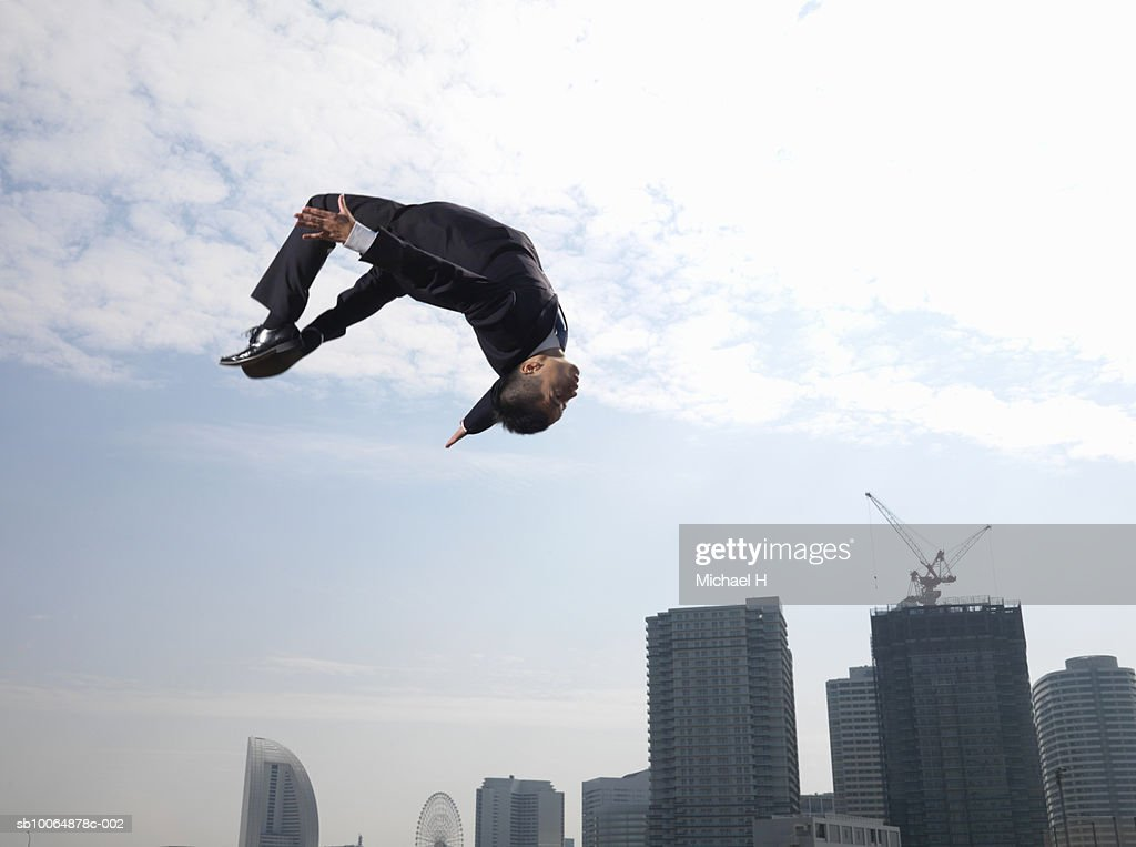 Businessman doing somersault, skyscrapers in background, low angle view : Stock Photo