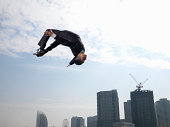 Businessman doing somersault, skyscrapers in background, low angle view