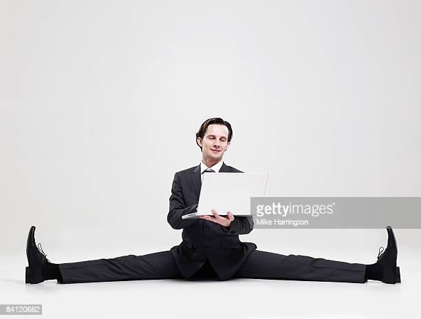 Businessman doing the splits holding laptop