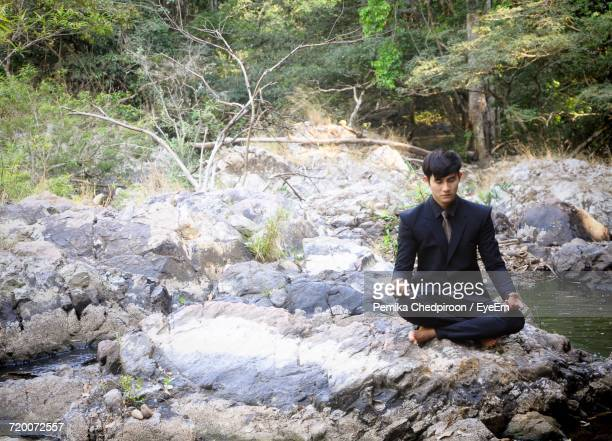 Businessman Doing Yoga On Rock By Stream At Forest