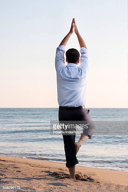 Businessman doing yoga on the beach