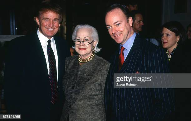 Businessman Donald Trump standing with two unidentified figures attends the opening for the new restaurant Daniel New York New York December 16 1998