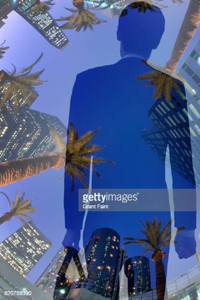 Businessman double exposure with office towers background.