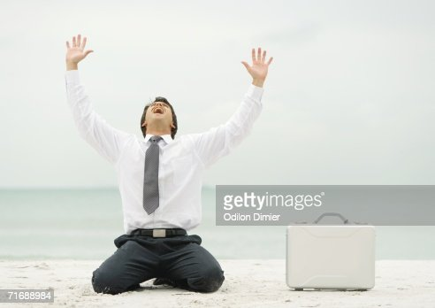 Businessman down on knees, shouting, on beach