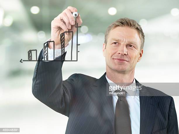 Businessman drawing bar chart on glass, smiling