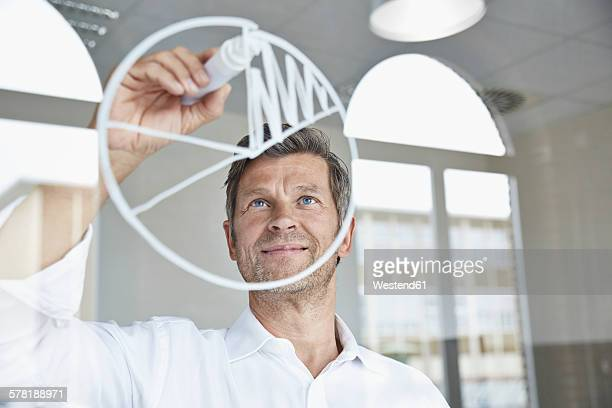 Businessman drawing diagram on glass pane in office