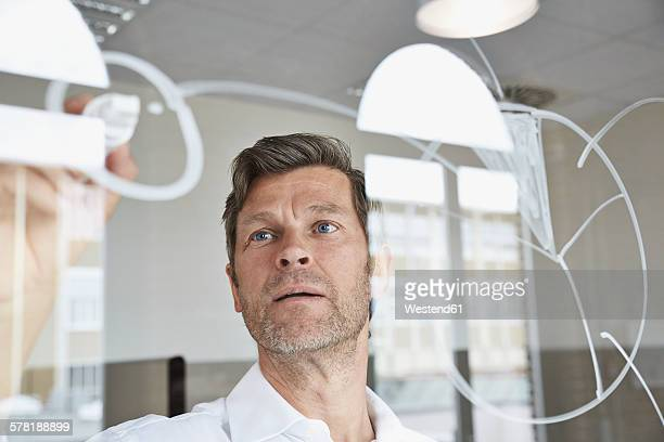 Businessman drawing diagrams on glass pane in office