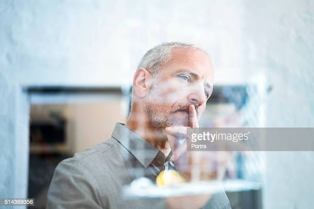 Businessman drawing graph on glass wall