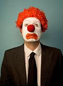 Businessman dressed as clown, looking sad, front view, portrait