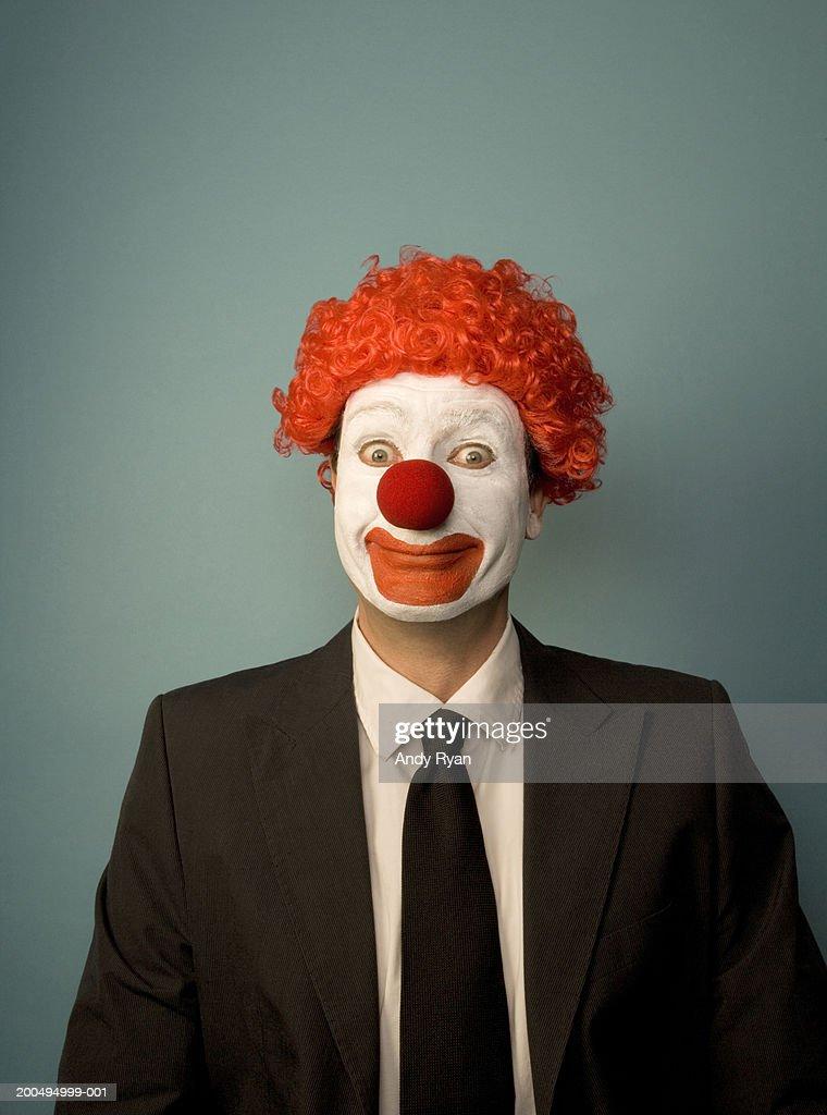 Businessman dressed as clown, smiling, front view, portrait