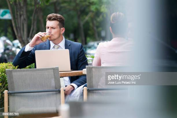 Businessman drinking and reading laptop at cafe outdoors