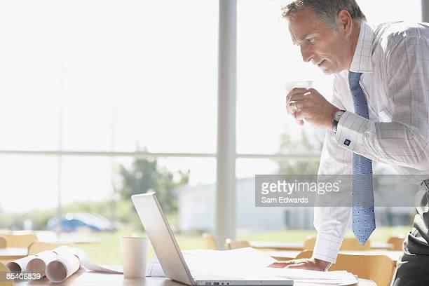 Empresario bebiendo y revisar blueprints