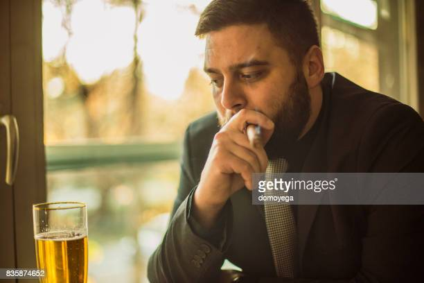 Businessman drinking and smoking cigar at the bar